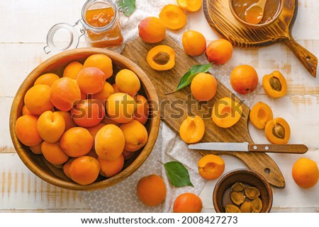 Tasty ripe apricots with jam on table Royalty-Free Stock Photo #2008427273
