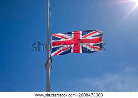 Union Jack flag flying at half mast against blue sky and sun. Royalty-Free Stock Photo #2008473080