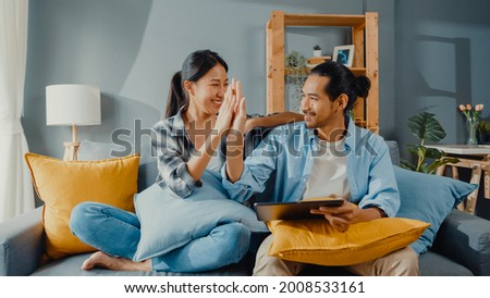 Happy asian young attractive couple man and woman sit on couch use tablet shopping online furniture decorate home in the living room at new house. Young married moving home shopper online concept. Royalty-Free Stock Photo #2008533161