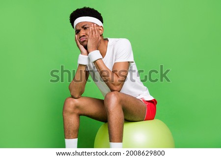 Photo of depressed offended sportsman guy sit ball look empty space wear white t-shirt isolated green color background