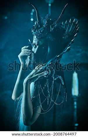 A portrait of a stately and beautiful old woman with long gray hair, in a rich headdress and a rich black dress and mask. Black Queen, Witch. Halloween. Royalty-Free Stock Photo #2008764497