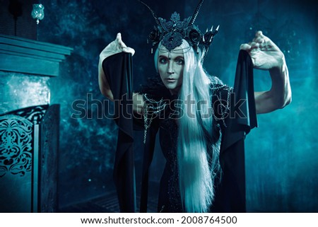 Stately and beautiful old woman with long gray hair, in a rich headdress and black dress against a dark background. Black Queen, Witch. Halloween. Royalty-Free Stock Photo #2008764500