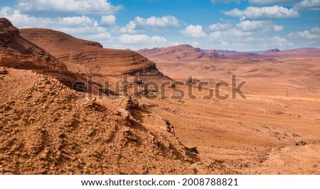 The austere beauty of the desolate Jbel Saghro mountain range, located in southern Morocco. A road is visible cut into the side of the rock on the left of the photo. Royalty-Free Stock Photo #2008788821