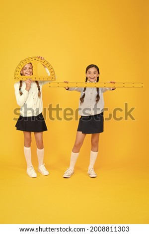 Learning school geometry. School children with measuring instruments on yellow background. Cute pupils holding protractor and ruler for school lesson. Small girls are back to school