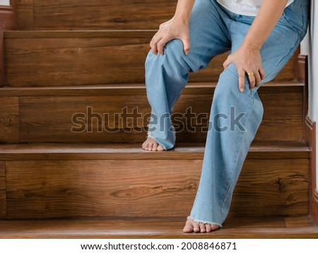 Woman stops for rest and leaning on wall for support while she cannot climb stairs with tingling legs. Concept of Guillain barre syndrome and numb legs disease or vaccine side effect.