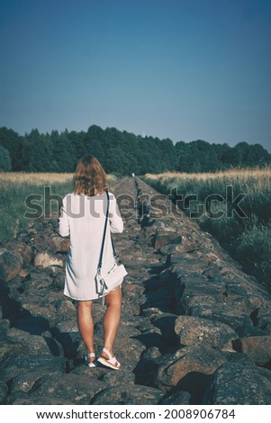 Woman in white dress walking along the stone pier at sunny hot day. High quality photo Royalty-Free Stock Photo #2008906784