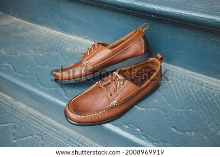 Brown leather boat shoes on a summertime blue fancy background.