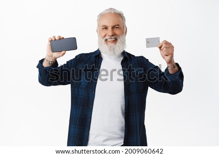 Happy bearded old man showing smartphone horizontal screen and credit card, recommending mobile application, banking app, standing over white background