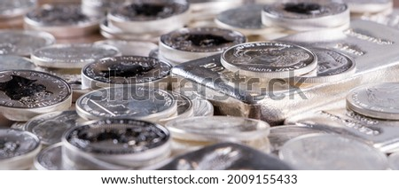Closeup of Silver bars and silver coins stacked on wooden table Royalty-Free Stock Photo #2009155433