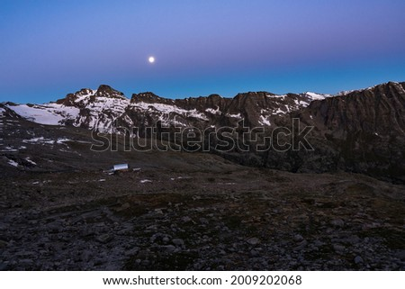 Nighttime with shining moon over a valley in the alps  Below is the Rifugio Vittorio Emanuele II mountain hut  Way to the Gran Pardiso summit  Royalty-Free Stock Photo #2009202068