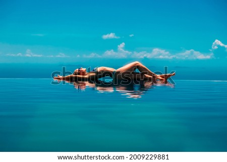 Happy girl have fun on summer beach holiday. Young woman relaxing at edge of infinity swimming pool with sea view from hill top. Healthy family lifestyle, summer travel with kids on tropical islands. Royalty-Free Stock Photo #2009229881
