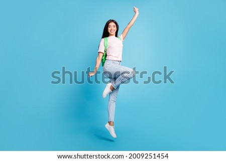 Full length body size view of attractive cheerful teen girl jumping going to high school isolated over bright blue color background Royalty-Free Stock Photo #2009251454