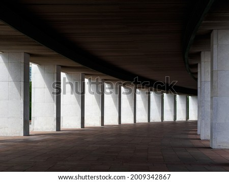 Long gallery of columns in the city building Royalty-Free Stock Photo #2009342867