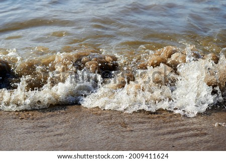 Sea wave with spray and foam near the shore. High quality photo Royalty-Free Stock Photo #2009411624