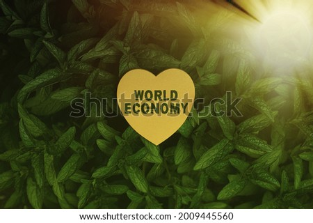 Conceptual caption World Economy. Conceptual photo international trading of product and services around the world Heart Shaped Paper On Top Of Outdoor Nature Leafy Plant Bush.