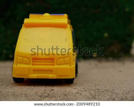 Toy police car in yellow color isolate at natural green blur wall backdrop, kids playing object natural image.