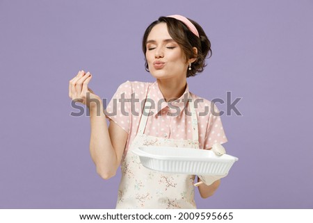 Young housewife chef cook baker woman in pink apron show cookies biscuits on baking form making okay taste delight sign, savoring, delicious isolated on pastel violet background. Cooking food concept. Royalty-Free Stock Photo #2009595665