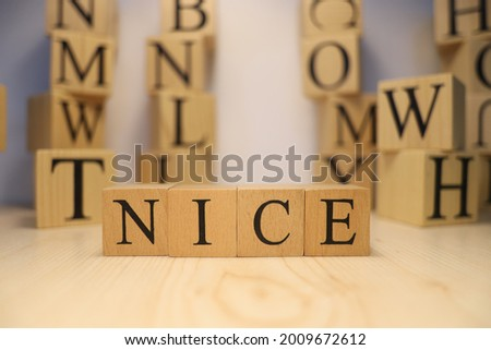 The word nice was created from wooden letter cubes. Cities and words. close up.