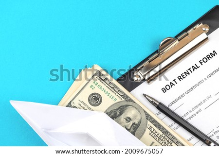 Boat rental appliaction form. Clipboard with official agreement, pen and money. Top view photo