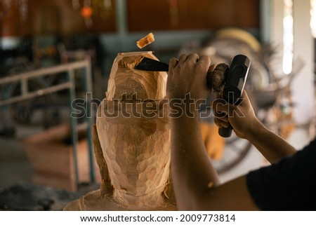 Wood buddha statue carved handmade by chisel. Asia craftsman professional carving with chisel in workshop. Carpentry woodwork. Handcraft carved. Selective focus. Royalty-Free Stock Photo #2009773814