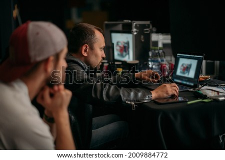 Editing director behind monitors on the set. A video editor edits video online while filming for a playback. Shooting shift, equipment and group. Modern photography technique.