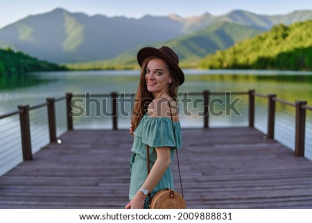 Portrait of happy cute smiling attractive traveler girl wearing hat and green dress standing alone on pier with lake and mountains view. Enjoying serene quiet peaceful atmosphere in nature Royalty-Free Stock Photo #2009888831