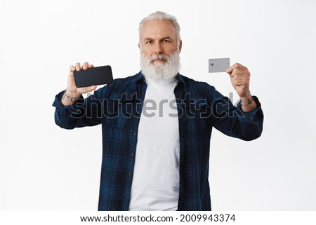Serious mature bearded man showing mobile phone screen and credit card, showing something on smartphone display, standing over white background