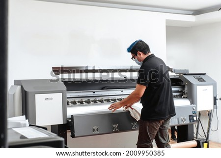 Latin American man with mask cleaning large format plotter. concept business and corona virus.