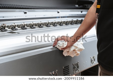 Person cleaning a printing plotter. Hands clean large format machine.