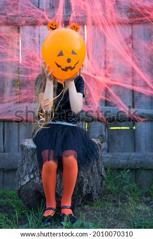 A little girl hid behind a balloon with a picture of Jack at the Halloween party