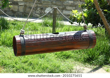 A tool to get natural fat from milk. Wooden churn hanging to make butter . A back view picture of a wooden butter churn in a also used for making ayran . Nehra made of ancient wood.
