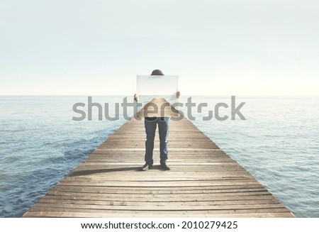 Man holding surreal painting of a boardwalk, abstract concept