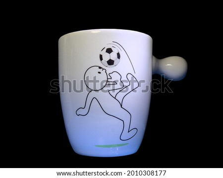 Man soccer playing football on white cup with light and black background.