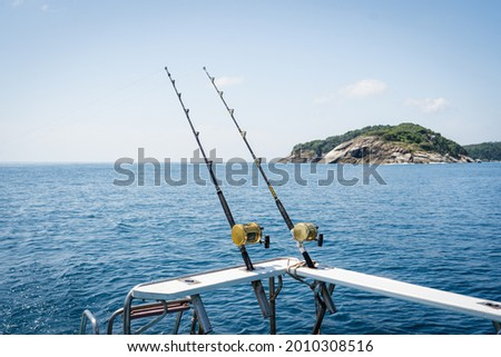 Fishing reels and rods reels for big game fishing trolling tuna.Big trawler fishing in the hot sea, blue sky and blue water.Andaman sea fishing, Phuket, Thailand.  Royalty-Free Stock Photo #2010308516
