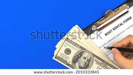 Man filling boat rental form. Clipboard with official agreement, pen and money. Top view photo