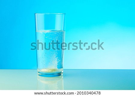 effervescent tablet dissolves in water. a glass of water and fizzy pill on blue background.