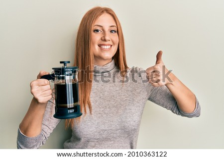 Young irish woman holding french coffee maker smiling happy and positive, thumb up doing excellent and approval sign