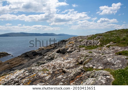 The West Cork rocky coastline covered with green grass and Irish sea moss. The Wild Atlantic Way route has a western coastline that is rugged, with many islands, peninsulas, headlands and bays.  Royalty-Free Stock Photo #2010413651