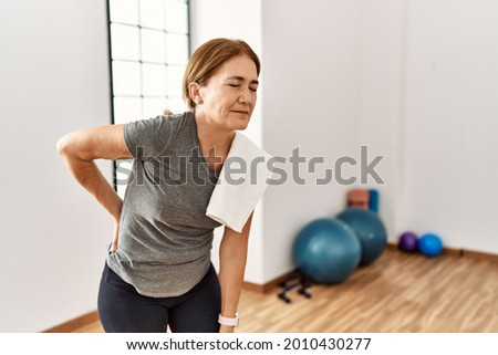 Middle age woman wearing sporty look training at the gym room suffering of backache, touching back with hand, muscular pain  Royalty-Free Stock Photo #2010430277