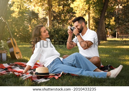 Man taking picture of his girlfriend on picnic plaid in summer park