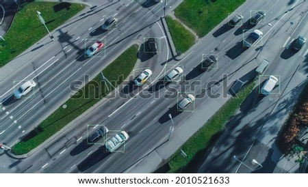 Aerial Drone Shot: Autonomous Self Driving Cars Moving On City Freeway. Concept: Artificial Intelligence Scans Cars and Pedestrians, Following Movement and Showing Data. Royalty-Free Stock Photo #2010521633