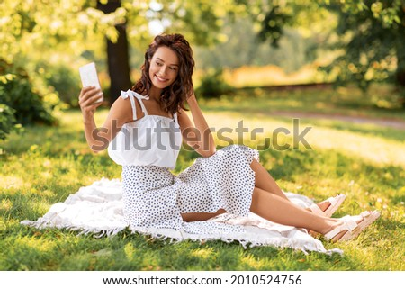 leisure and people concept - happy smiling young woman with smartphone sitting on picnic blanket and taking selfie at summer park
