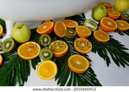 the milk bath is decorated with tropical fruits. bath for taking pictures of children