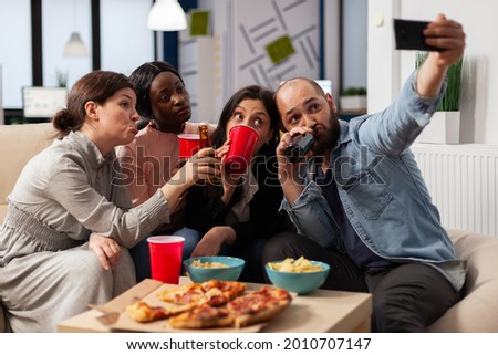 Multi ethnic team of friends make memories at after work party taking pictures on smartphone. Coworkers celebrating at office space with snacks pizza chips cups of drinks on table