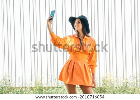 girl with hat and dress taking pictures with mobile phone