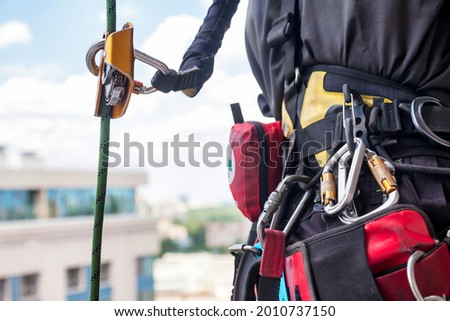 Equipment of industrial mountaineering worker on roof of building during industrial high-rise work. Climbing equipments before starting job. Rope laborer access. Concept of urban works. Copy space Royalty-Free Stock Photo #2010737150