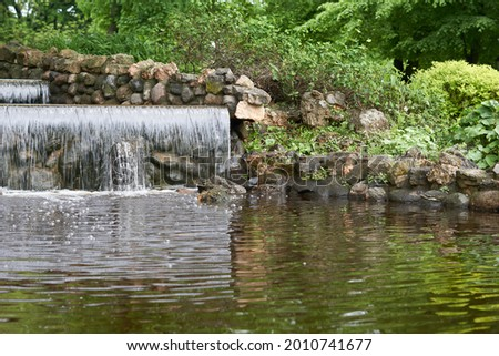artificial waterfall in public park . High quality photo Royalty-Free Stock Photo #2010741677