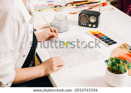 Young woman coloring page antistress at table indoors, mental wellbeing and art therapy. Woman paints a sketch, meditative process of coloring pages. Royalty-Free Stock Photo #2010765596