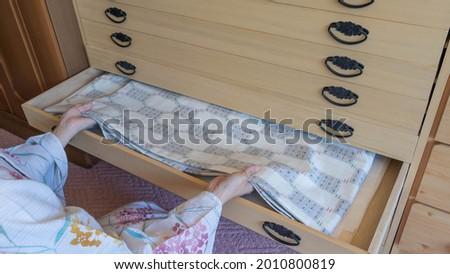 "Japanese woman wearing a ""yukata"".Storage of Japanese kimono. Paulownia chest. Royalty-Free Stock Photo #2010800819"