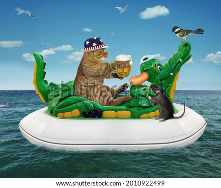 A beige cat in a straw hat with a mug of beer is floating on an inflatable crocodile in the sea at a resort.